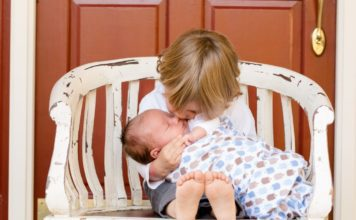 big brother holding a newborn baby on a bench