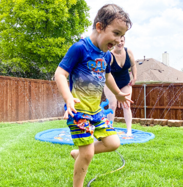 child running in sprinklers during summer when it's too hot outside