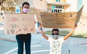 black mom and black child holding protest signs
