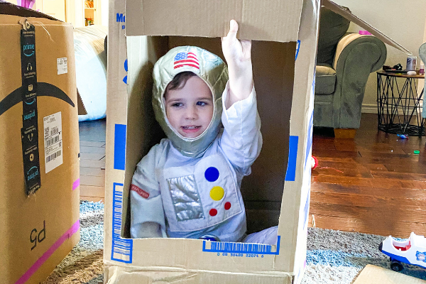 kids playing dress up in cardboard boxes