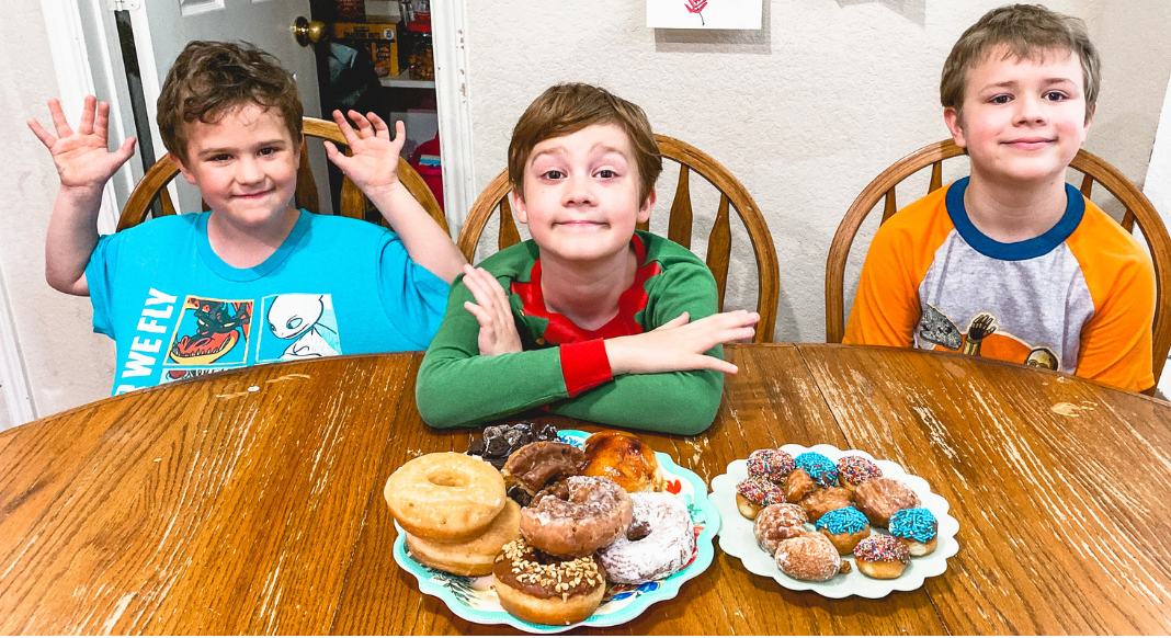 Boys sitting at a table with donuts in Allen, Texas