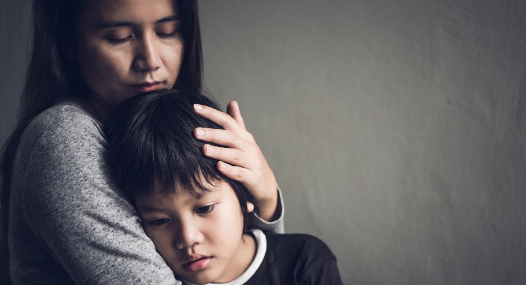 mother hugging sad child